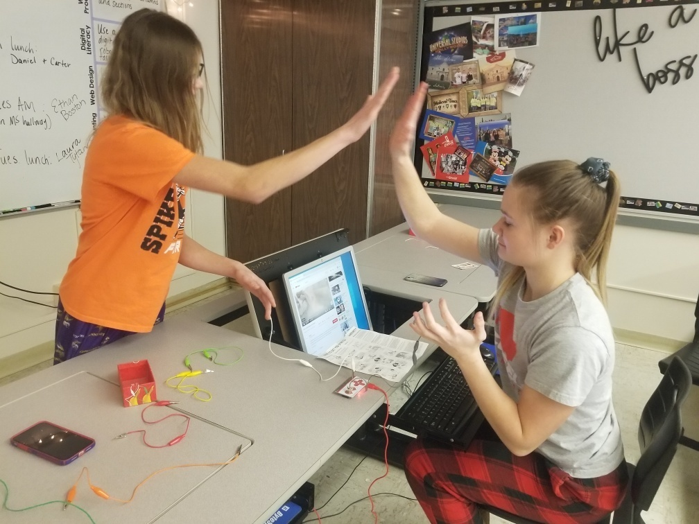 Students using a Makey-Makey as a mouse to start and stop a video by clapping hands.